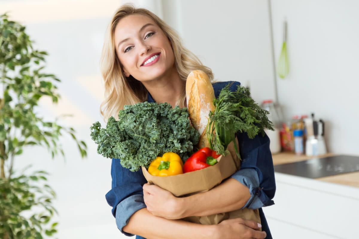 Uśmiechnięta kobieta z zakupami. Dieta w sportach wytrzymałościowych.