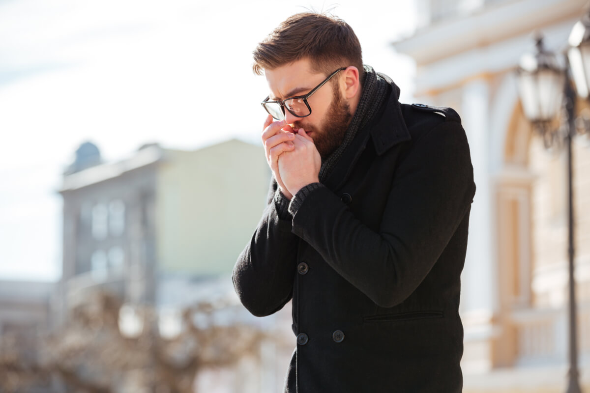 Mężczyzna chucha w dłonie. Jak skutecznie przygotować się na sezon grypowy