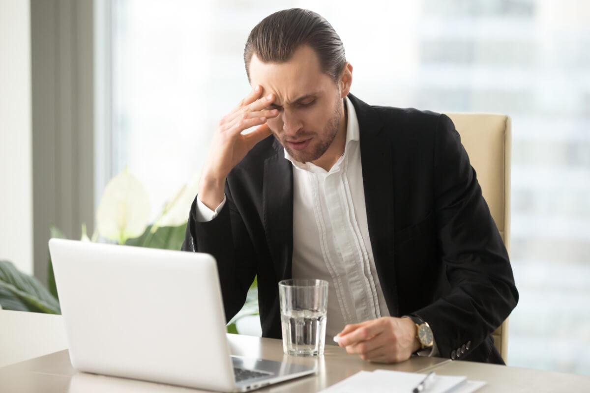 Mężczyzna z bolącą głową, przed laptopem. Skuteczne sposoby na kaca
