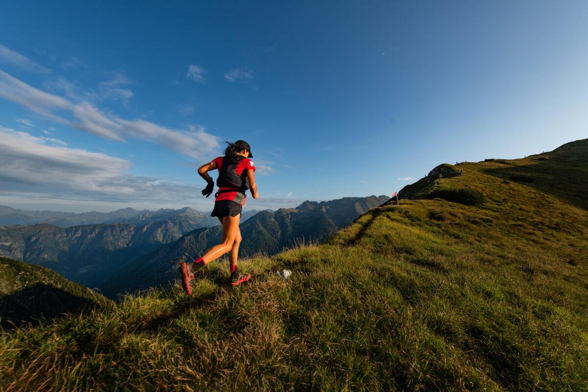 Kobieta biegnie przez połoniny. Dieta w sportach wytrzymałościowych - czego nie może zabraknąć