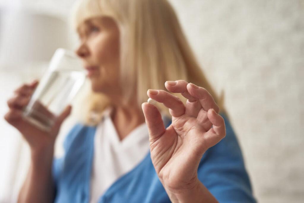 Kobieta trzyma w dłoni tabletkę. Terapia hormonalna u kobiet - skutki uboczne i zagrożenia.