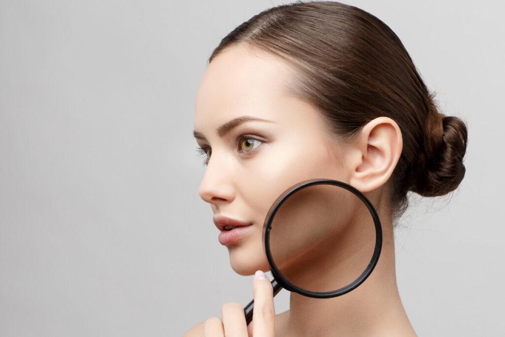 Piękna kobieta z lupą przy policzku. Jak zadbać o skórę po lecie - zabiegi wspierające regenerację