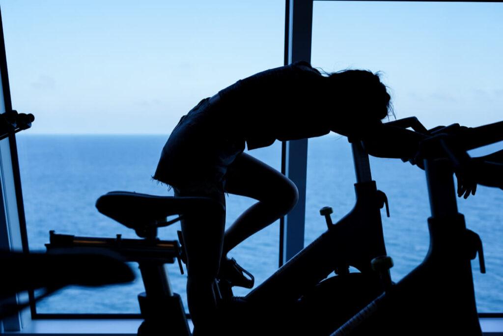 Zmęczona dziewczyna na rowerku treningowym. Jak uniknąć przetrenowania i osiągnąć lepsze wyniki