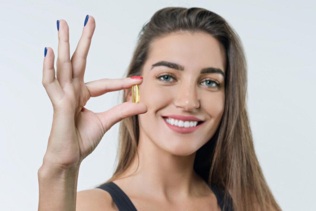 Młoda kobieta trzyma w dłoni kapsułkę z witaminami. Witamina D - jak bardzo jej potrzebujemy