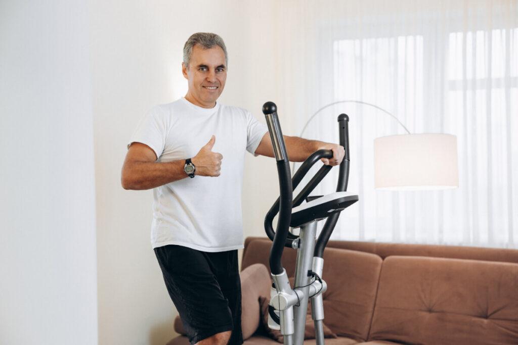 Мужчина тренируется на эллиптическом кросс-тренажере. Домашнее кардио-оборудование - что выбрать?