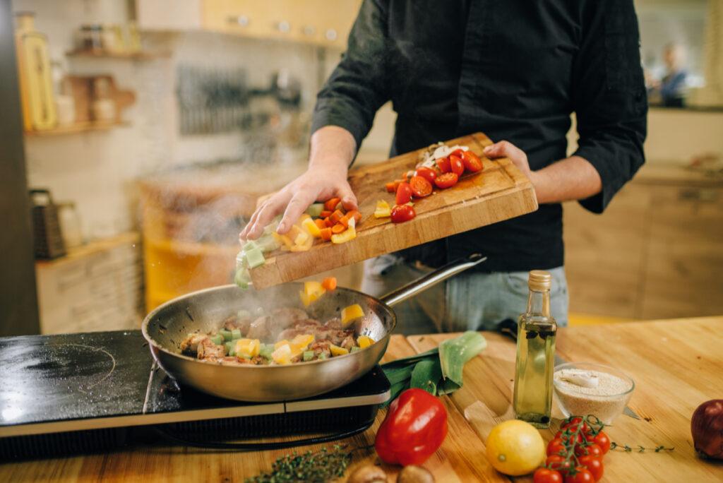 Mężczyzna przygotowujący posiłek. Jak dieta przy Hashimoto - czyli co jeść, a czego unikać?