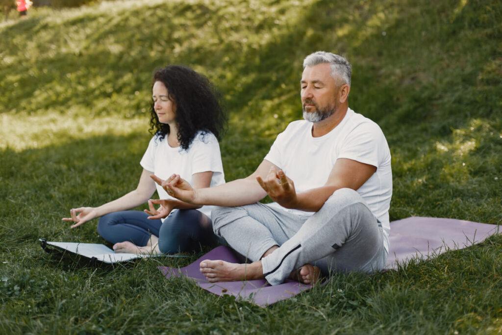 Para w starszym wieku medytuje na łonie natury. Ty też możesz spowolnić proces starzenia się