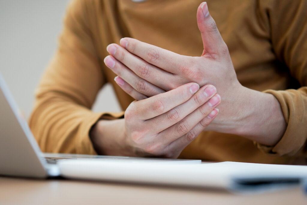 Mężczyzna przy laptopie trzyma się za bolącą dłoń. Zespoły przeciążeniowe układu ruchu - przyczyny i sposoby regeneracji