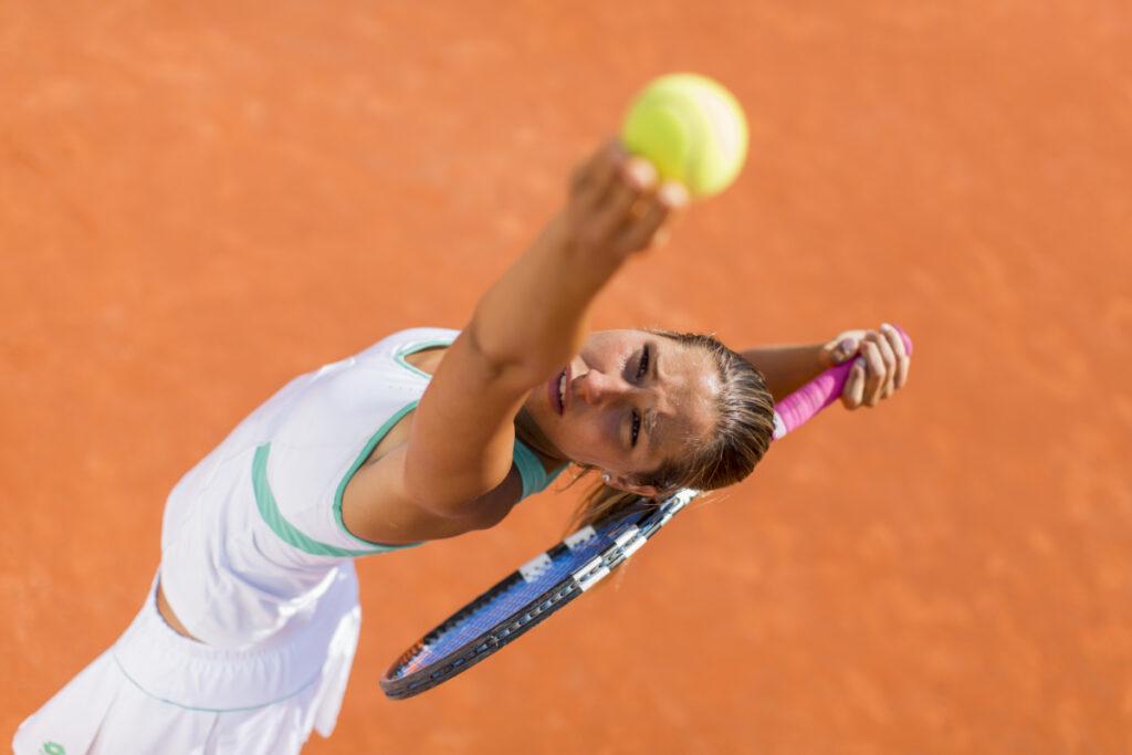 Młoda tenisistka w trakcie serwu. Zespoły przeciążeniowe układu ruchu - przyczyny i sposoby regeneracji