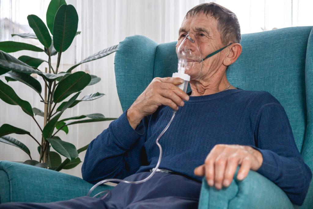 Starszy mężczyzna w masce tlenowej. Przewlekła niewydolność oddechowa.