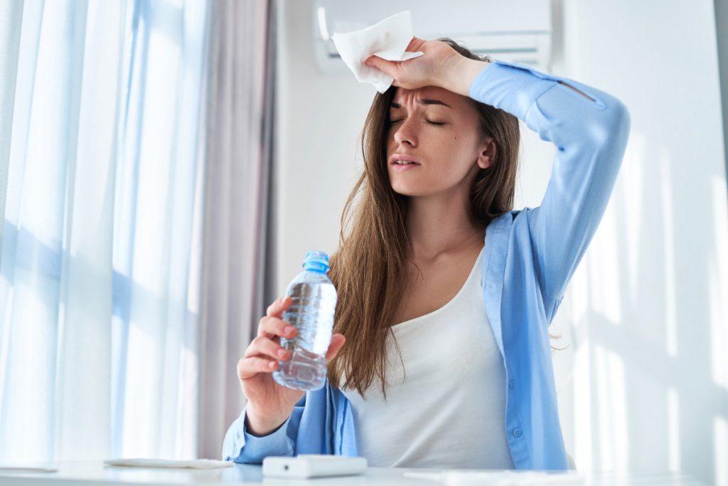 Kobieta pije wodę i trzyma się za głowę. Odwodnienie organizmu - co robić, by do niego nie dopuścić.