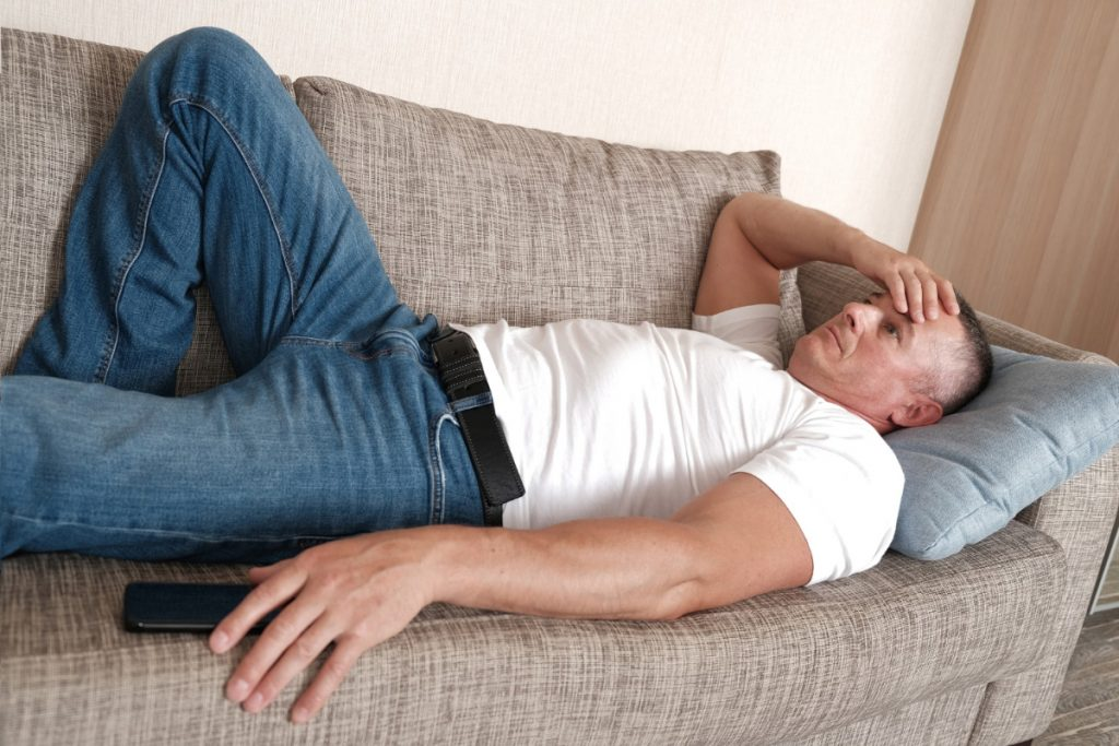 Mężczyzna na łóżku. Zmęczenie i brak energii - przyczyny
