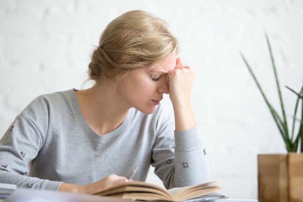 Zmęczona kobieta nad pochylona nad ksiażką. Zmęczenie i brak energii - co może być przyczyną