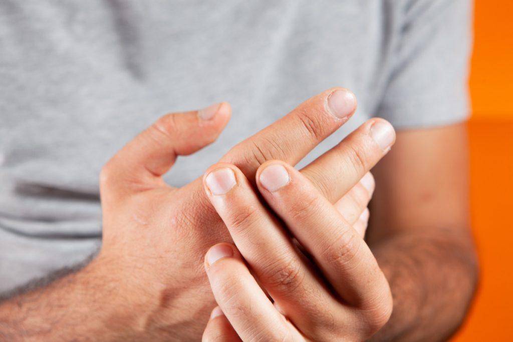 Mężczyzna trzyma się za dłoń. Choroba zwyrodnieniowa stawów - jak się objawia